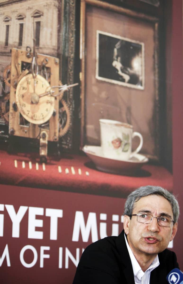 Orhan Pamuk museon mainosjulisteen edessä.