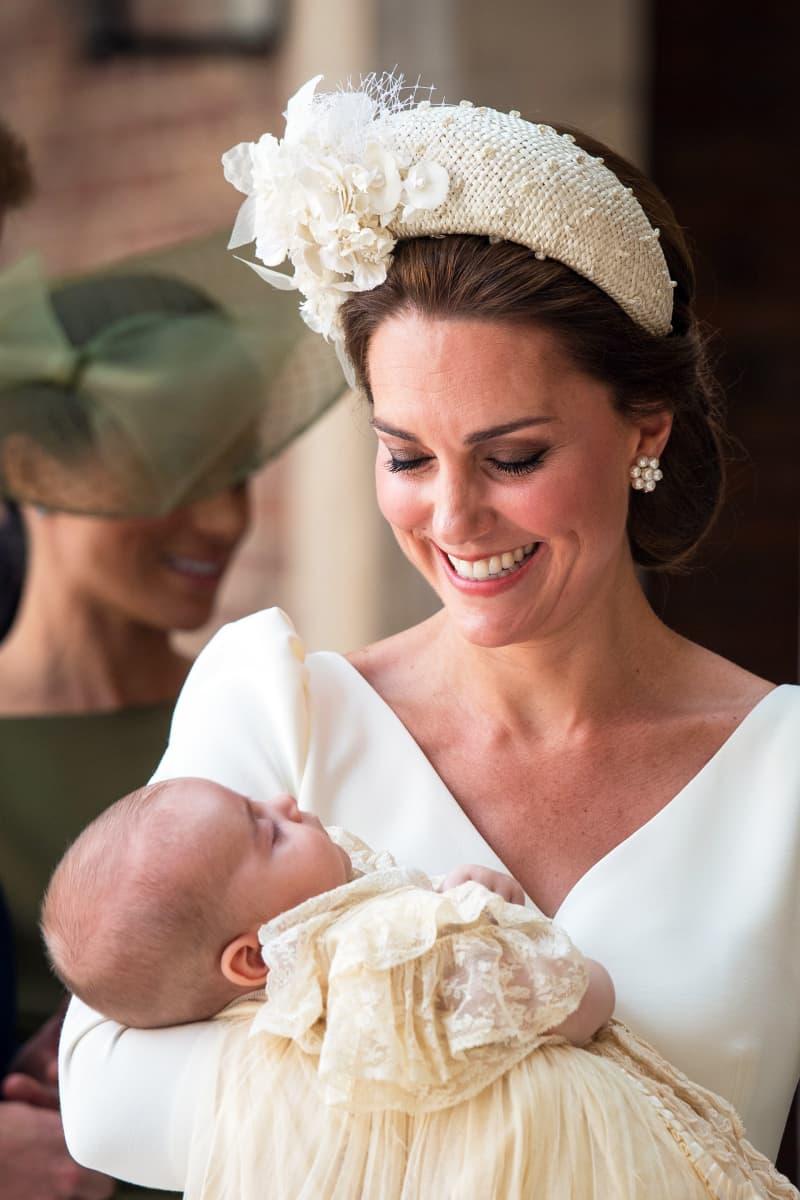 Cambridgen herttuatar Catherine sylissään prinssi Louis kastemekossaan. Taustalla näkyy Sussexin herttuatar Meghan.