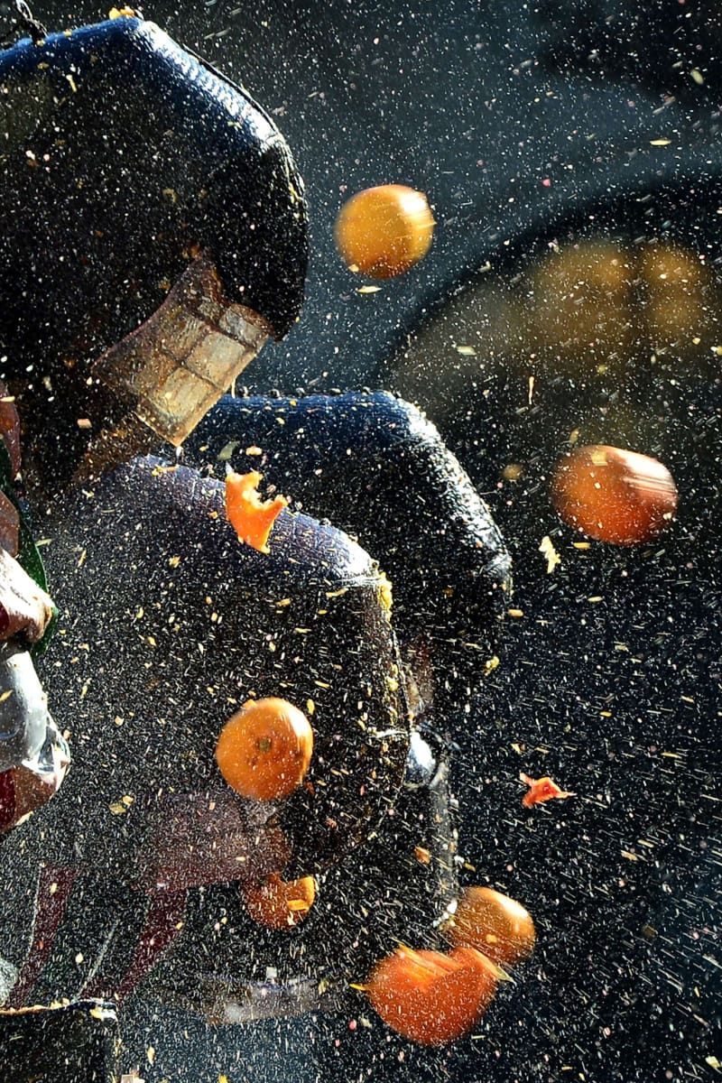 """Ihmiset heittelevät kypäräpäisiä miehiä appelsiineilla perinteisen """"Appelsiinien taistelun"""" aikana."""