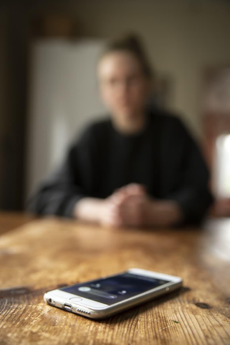 Puhelin soi pöydällä, ihminen näkyy taustalla sumennettuna.