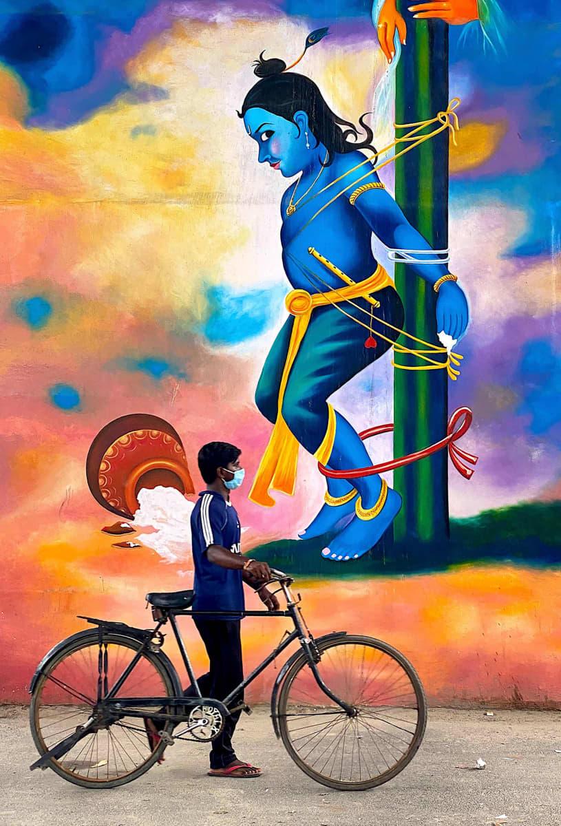 Kuvassa on värikäs muraali ja henkilö sen edessä seisomassa.