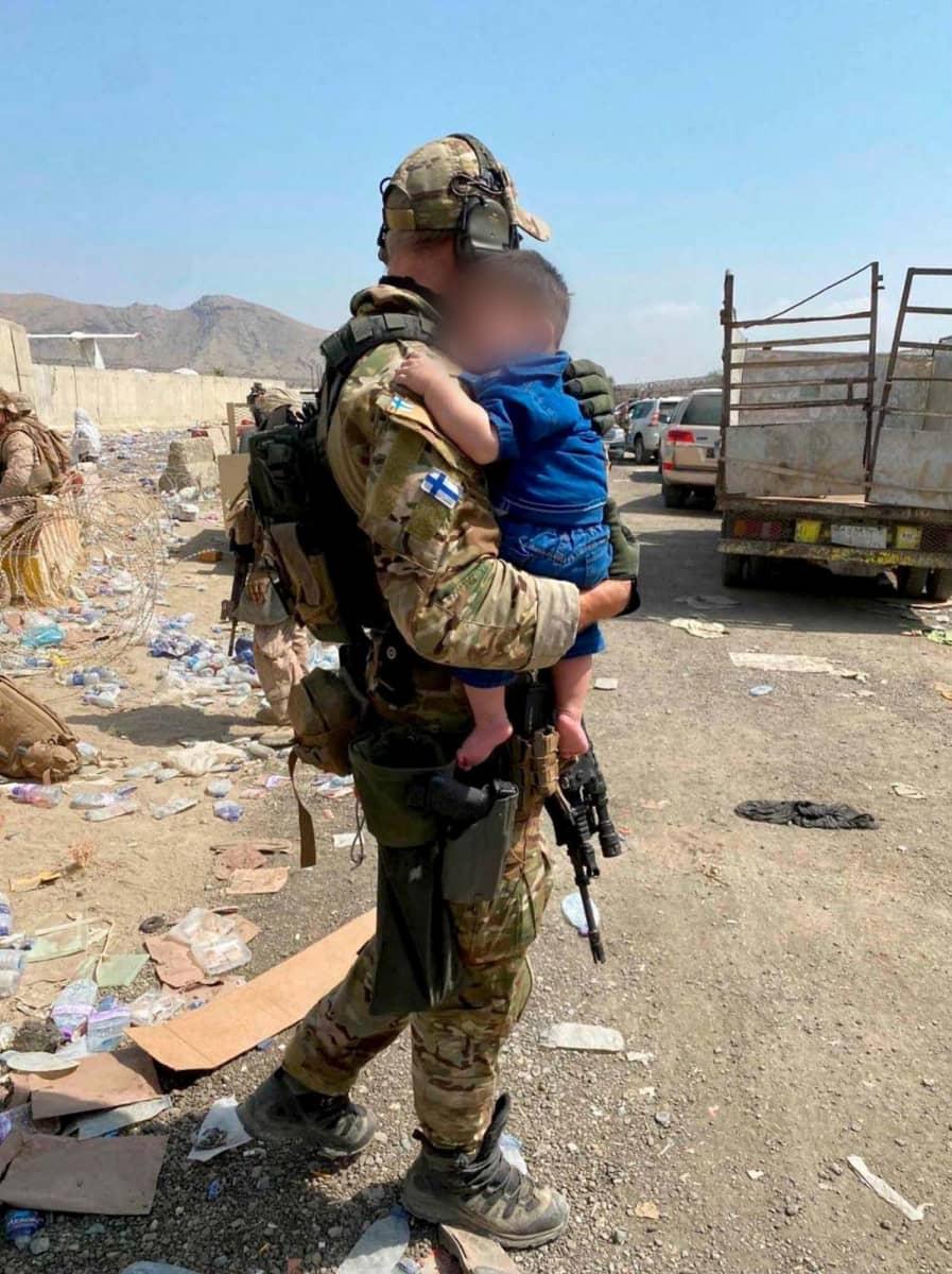Suomalainen sotilas Kabulin lentokentällä lapsi sylissään.