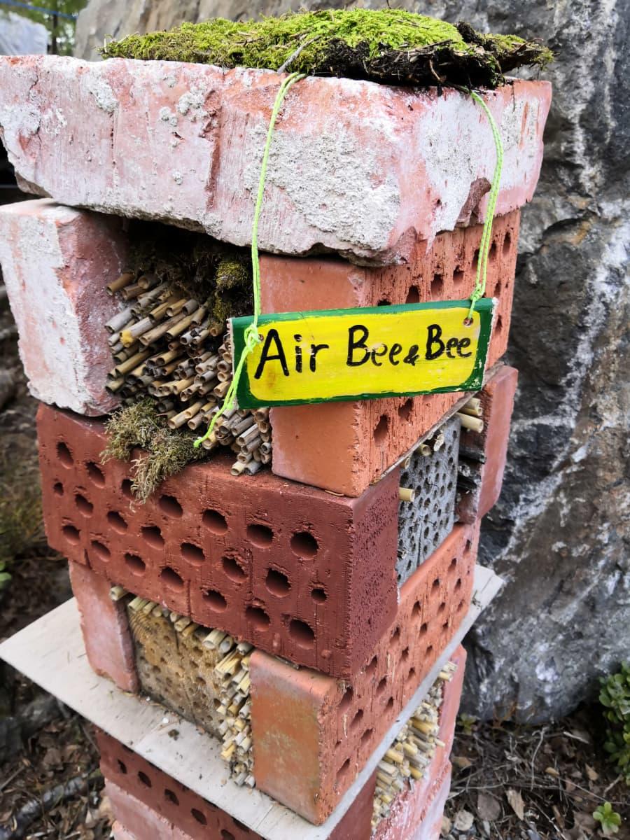 Tiilistä koottu hyönteishotelli bee&bee-kyltillä.