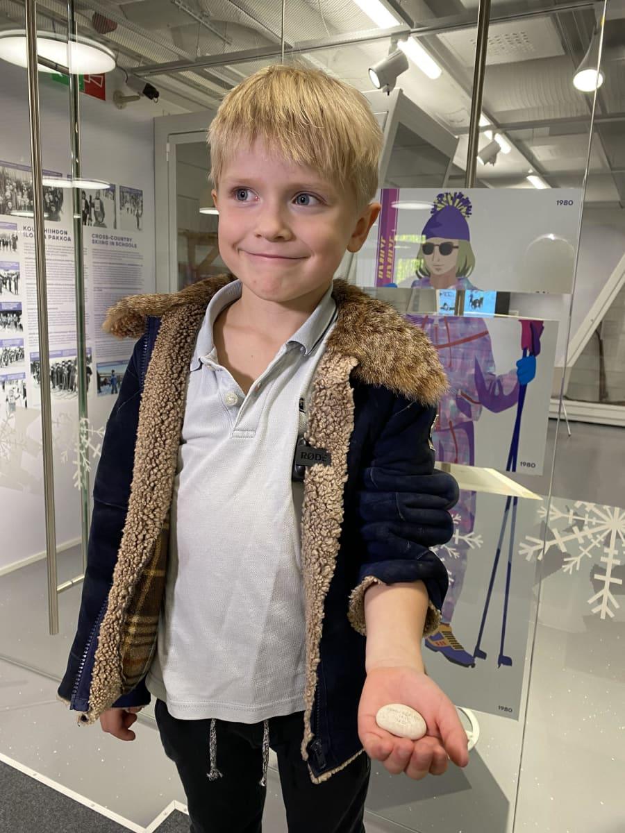 6-vuotias Ahti Valola hymyilee. Hänellä on vasemmassa kädessään vaalea kivi, jossa on kirjoitusta ja numeromerkintöjä. Taustalla kuvia Lahden Hiihtomuseon näyttelystä.