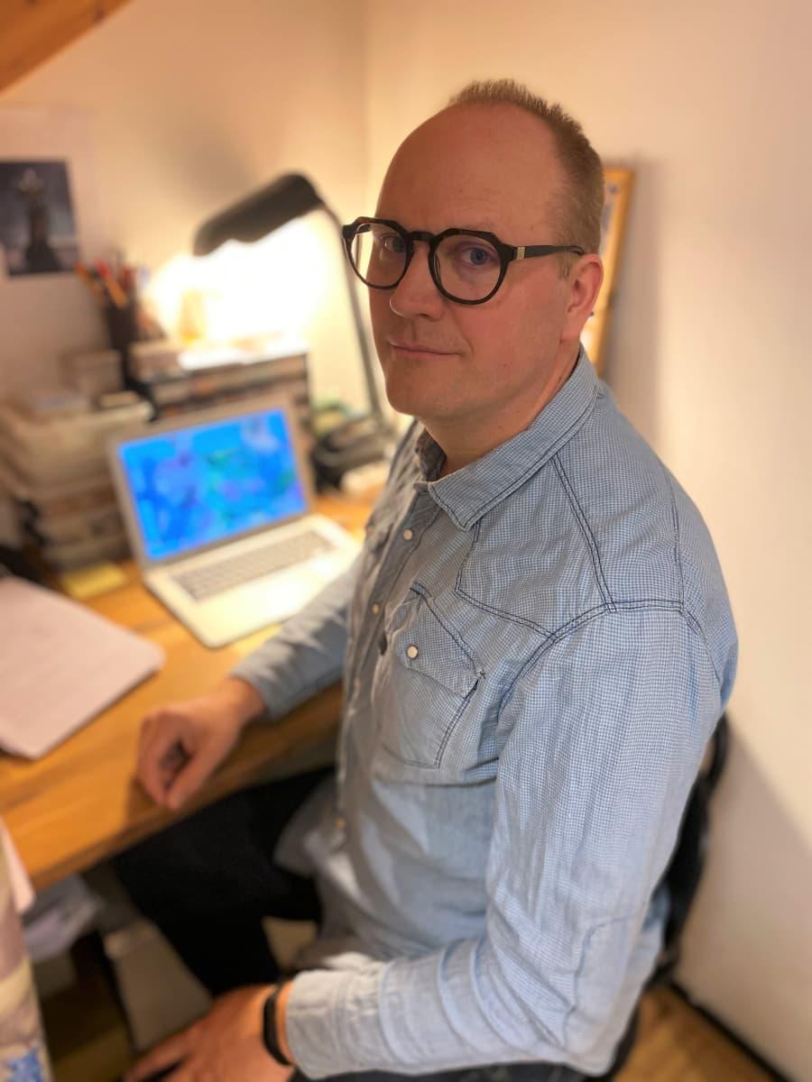 Agemonia-lautapelin suunnitellut Max Wikström istuu pyöreäsangaiset silmälasit päässä kannettavan tietokoneen äärellä
