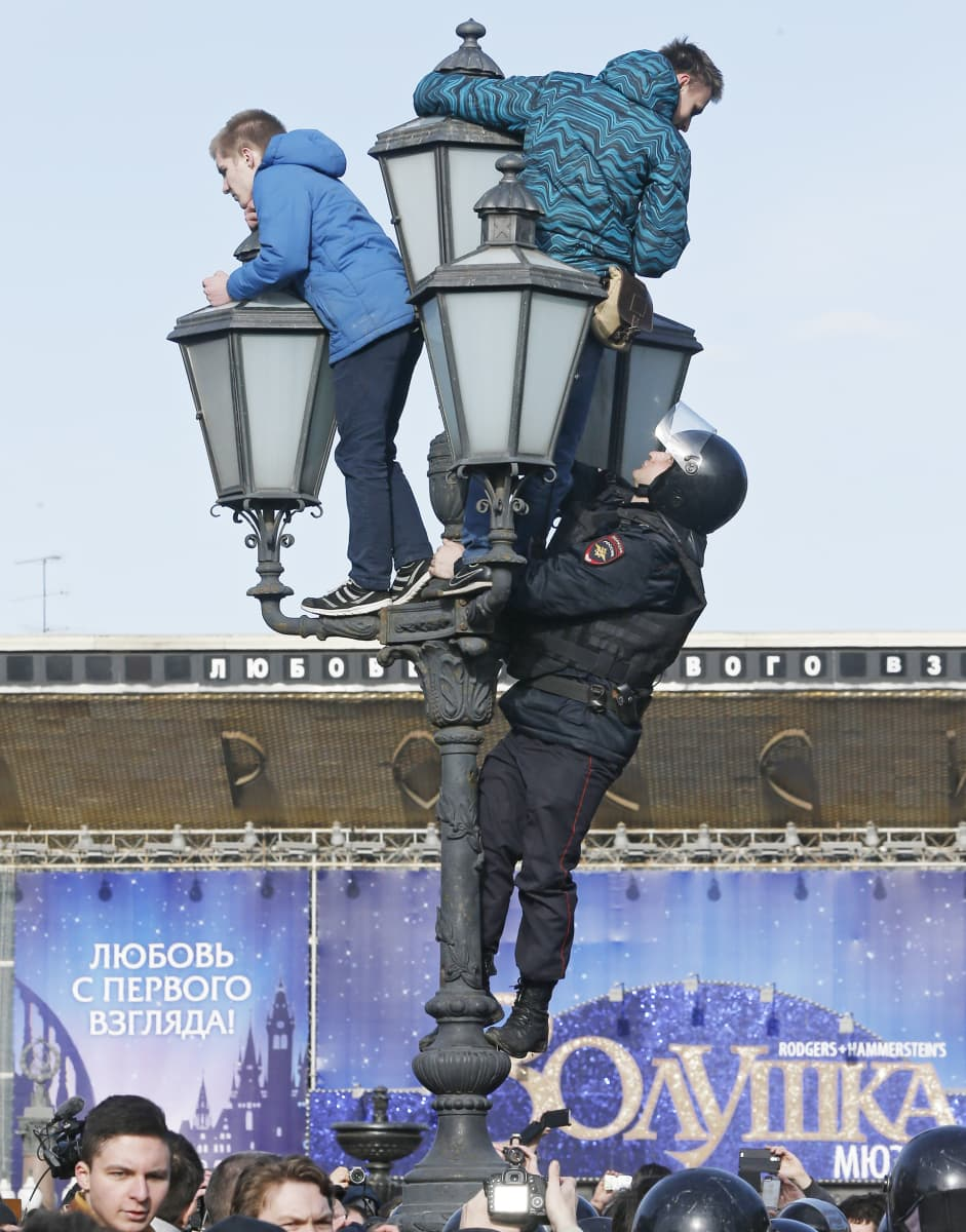 Poliisi kiipeä mielenosoittajien perässä lyhtypylvääseen Moskovassa.