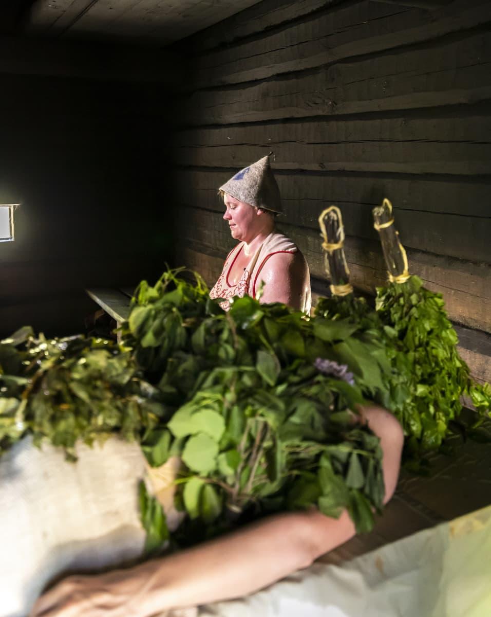 Perinnesaunottaja istuu vihdonnan jälkeen vihtoihin peitetyn naisen takana savusaunassa.