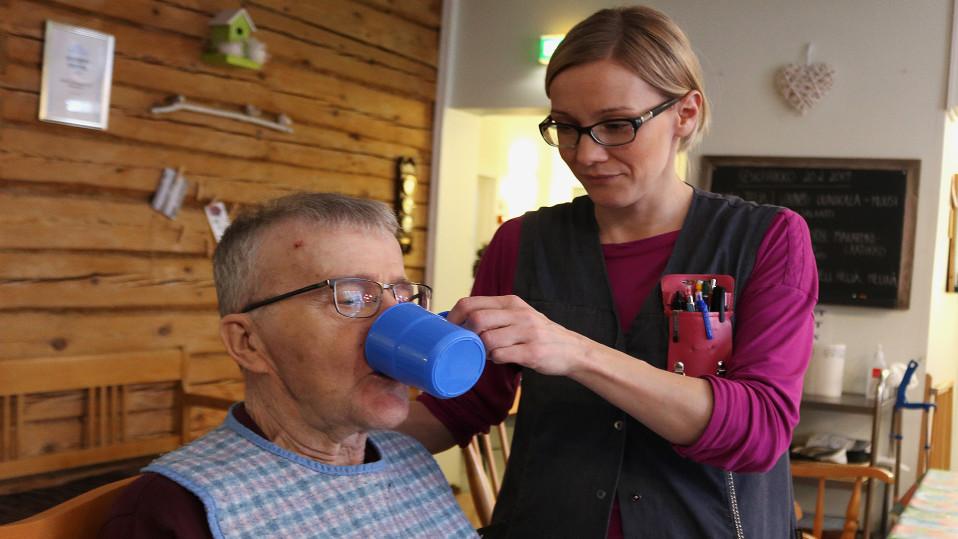 Tuija Juga auttaa asukasta juomaan