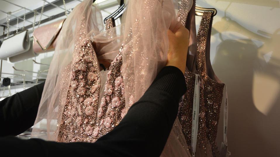 Kuvassa nainen asettelee mekkoa henkarilla