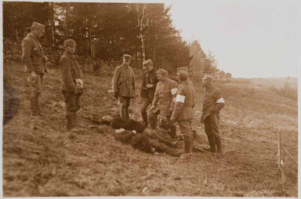Säkkijärvi. Pohjois-Savon rykmentin suojeluskuntalaiset tarkastelevat teloittamiensa punakaartilaisten ruumiita.