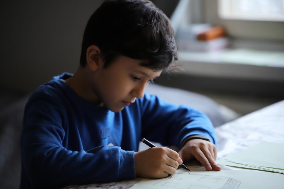 Poika piirtää.
