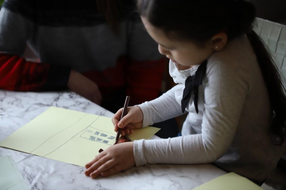 Tyttö piirtää taloa.