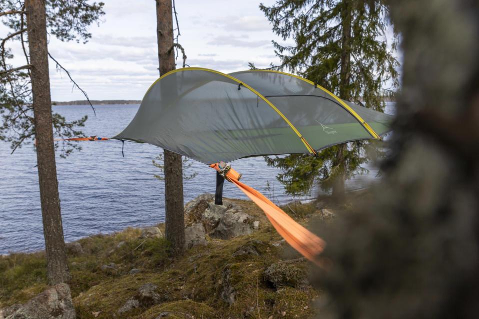 Tentsilen teltta pingotettuna ilmaan puiden väliin Kyyjärven leirintäalueen rantamaisemassa