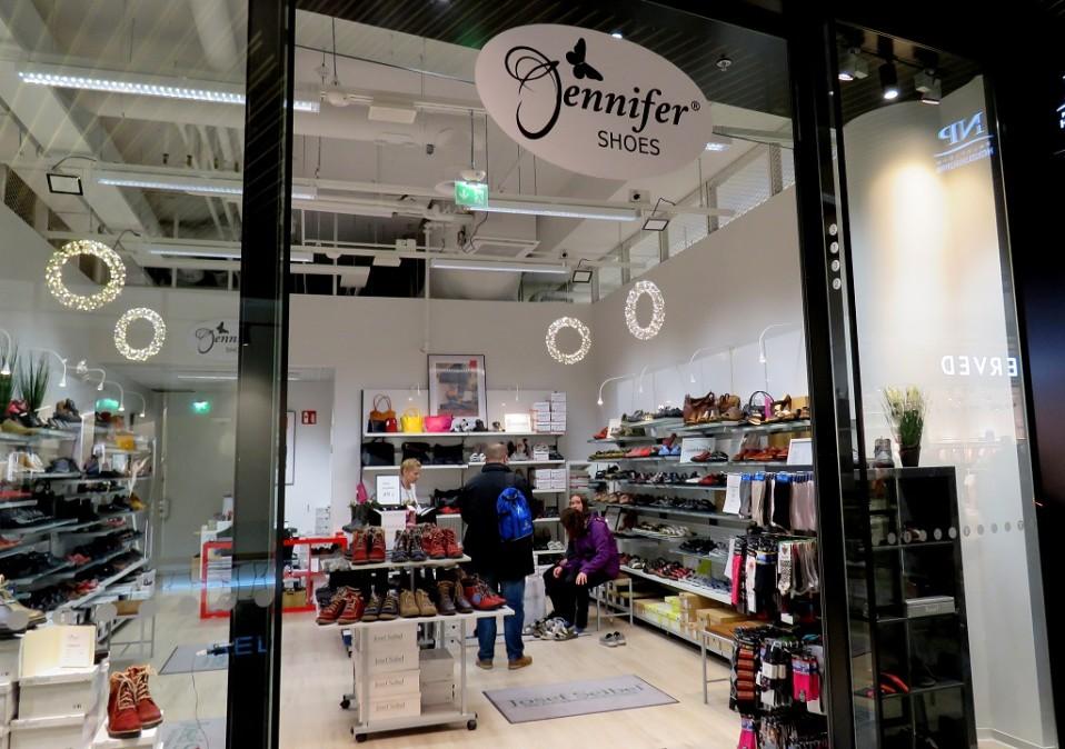 Jennifer Shoes -niminen kenkäkauppa, jossa isä ja kaksi tytärtä sovittelevat kenkiä.