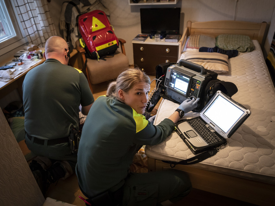 Ambulanssin henkilökuntaa vanhuksen makuuhuoneessa.