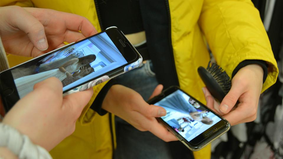 Kuvassa kaksi tyttöä katsoo kännykältä pukuja