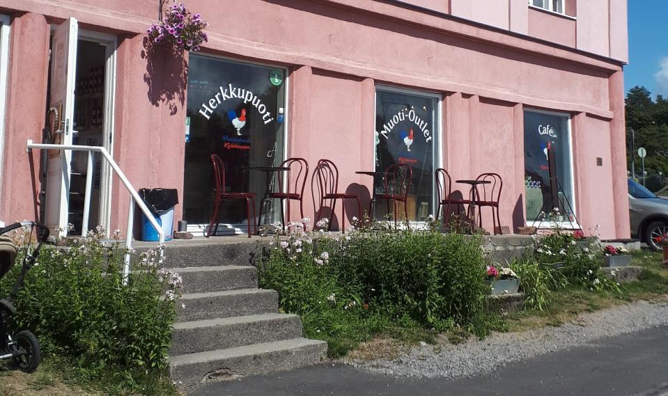 Vanhanaikainen vaaleanpunainen kivitalo, jonka alakerran ikkunoissa on kaupan ja ravintolan teippaukset