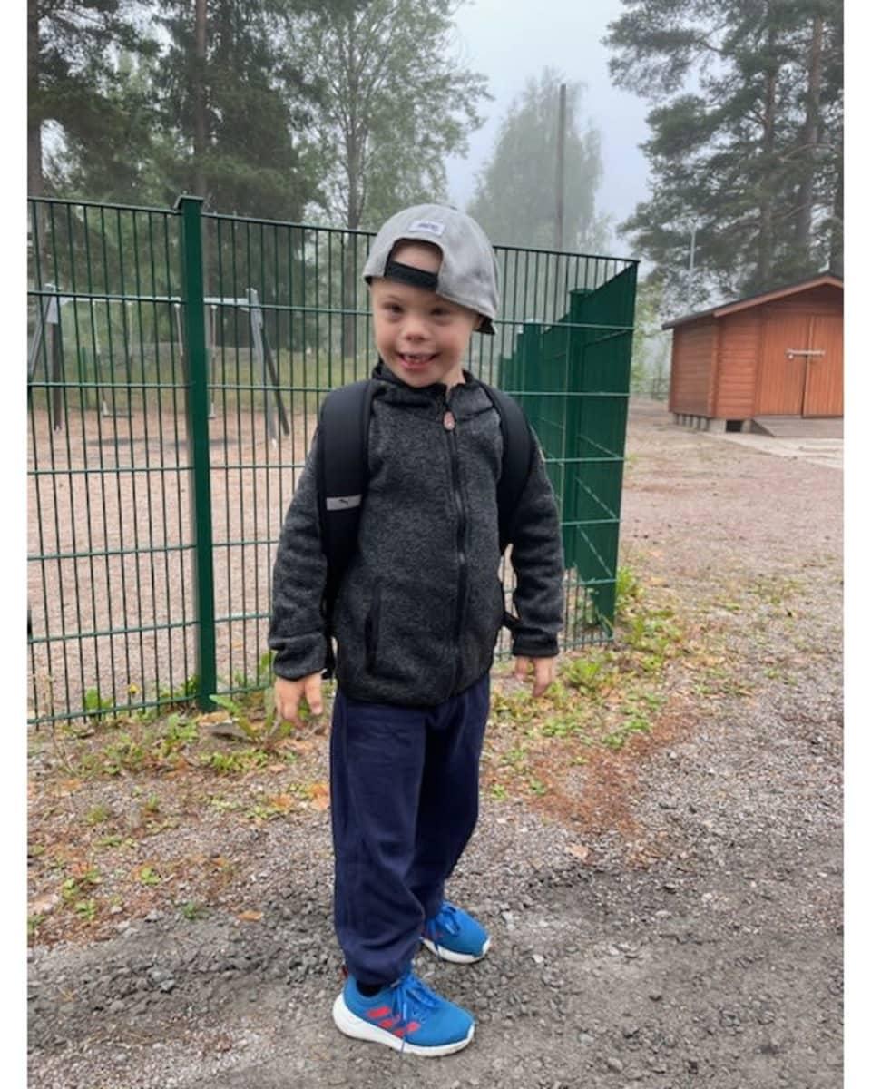 Pieni poika seisoo koulun aidan edessä