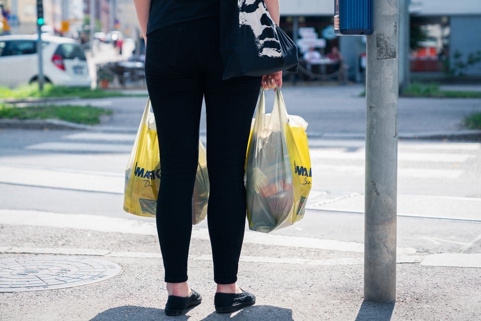 Nainen kantaa kahta muovikassia.
