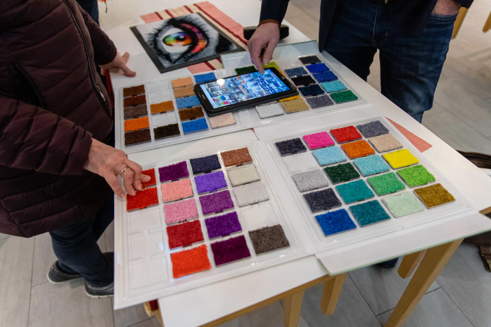 Mattojen värikkäitä näytepaloja pöydällä.