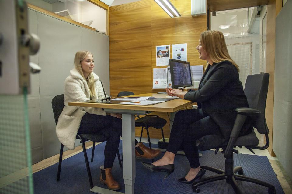 Pohjois-Savon Osuuspankin asiakasneuvoja Julia Jerkku keskustelee raha-asioista Kuopiolaisen nuoren Olivia Honkosen kanssa.