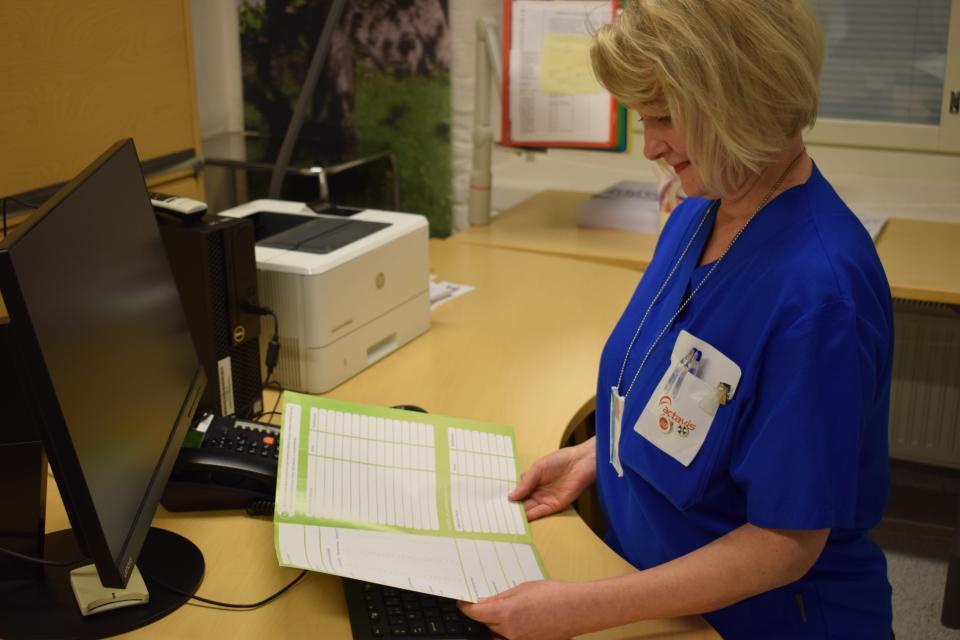 Sairaanhoitaja Marika Riihikoski lukee paperia.