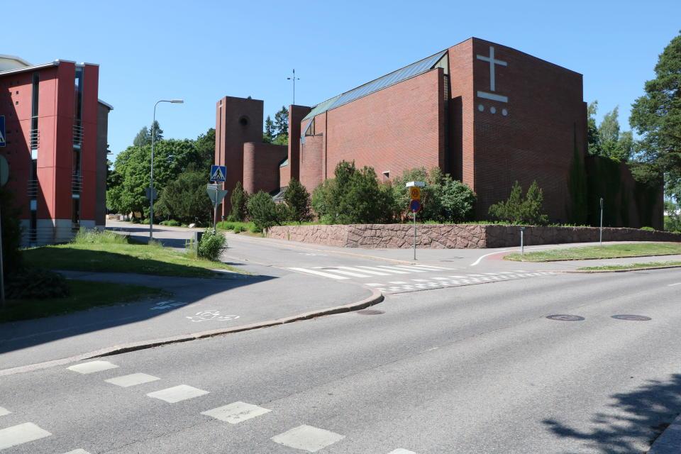 Vägkorsning i Övre Malm i Helsingfors. I bakgrunden finns en kyrka med ett stort kors på väggen.