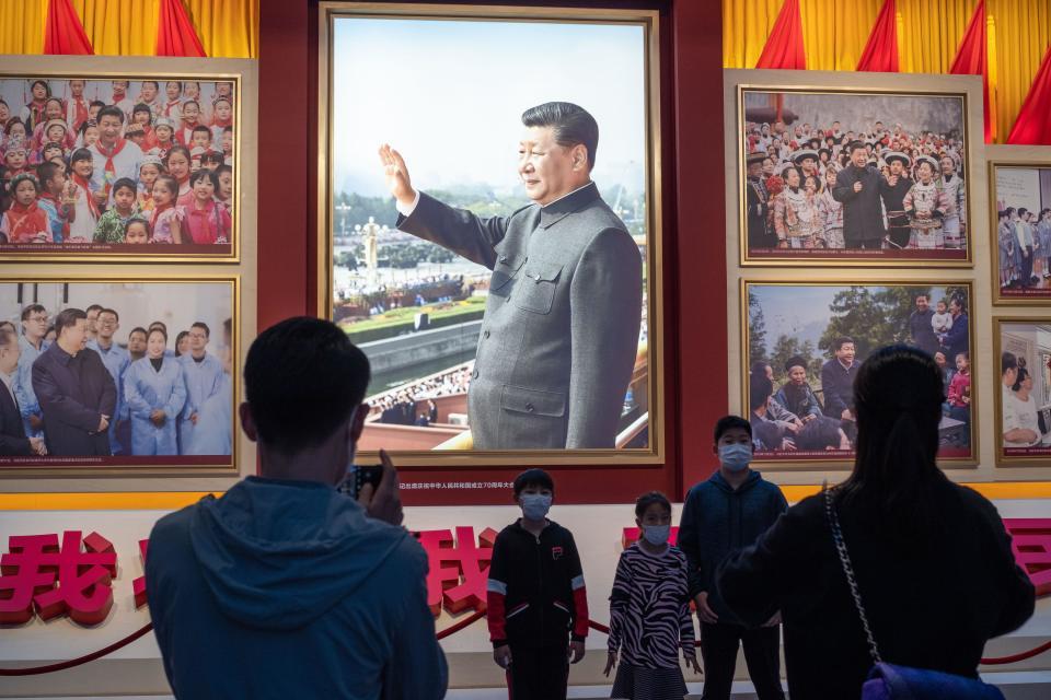 Joukko ihmisiä katsoo Xi Jinpingin kuvaa Kiinan kommunistisen puolueen museossa.