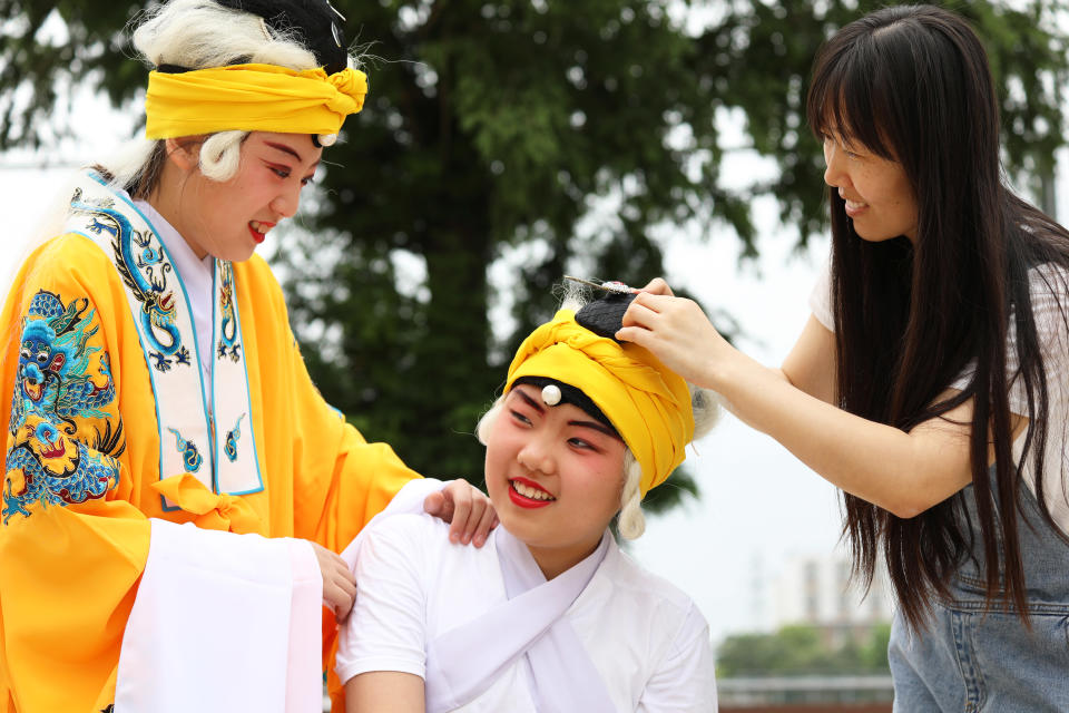 Nuorta tyttöä puetaan kiinalaisen oopperan pukuun, päässä on keltainen turbaanin näköinen asuste.