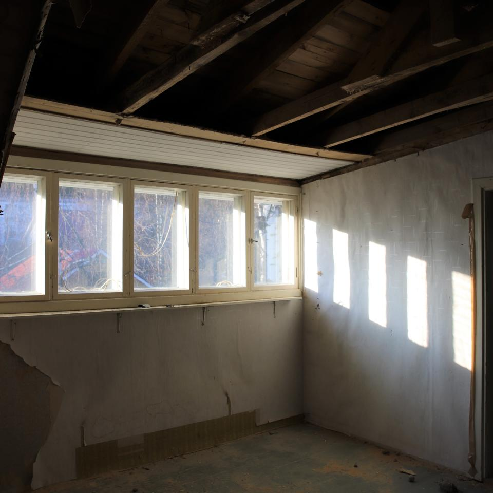 Vanhan talon yläkerran ikkunoista tulee valoa sisälle.
